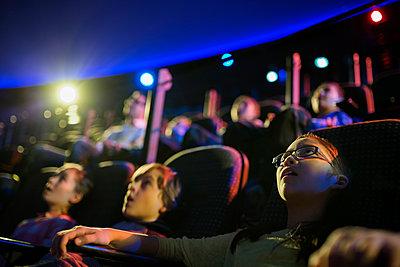 Surprised students enjoying planetarium show - p1192m1019865f by Hero Images