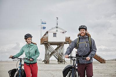 Pärchen mit Trekking-Bikes in Sankt Peter-Ording und am Westerhever Leuchtturm - p300m1416713 von Roger Richter