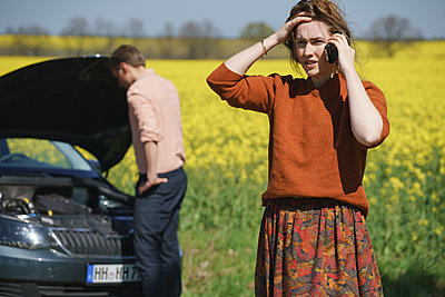 Worried woman talking on phone while man repairing car in background on sunny day - p301m1148363 by Halfdark