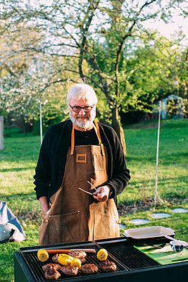Man barbecuing in garden - p312m1557044 by Anna Rostrom