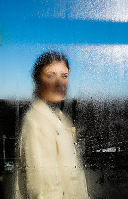 Sweden, Young woman in coat behind wet window - p352m1186948 by Lena Katarina Johansson