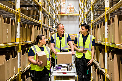 Multi-ethnic coworkers discussing while walking with cart on aisle amidst racks at distribution warehouse - p426m2018825 by Maskot