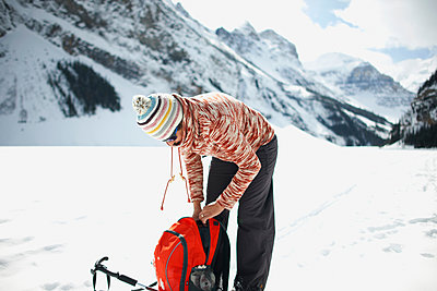 Hiker snow covered landscape preparing hiking equipment, Lake Louise, Canada - p429m1417889 by Peter Muller
