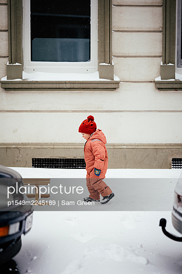Toddler boy with bobble cap in the snow - p1549m2245189 by Sam Green
