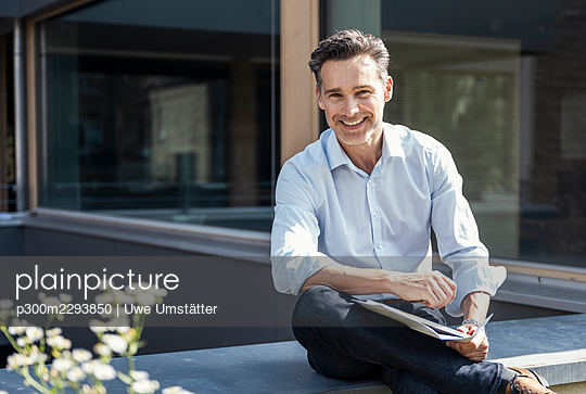 Smiling businessman sitting on retaining wall - p300m2293850 by Uwe Umstätter
