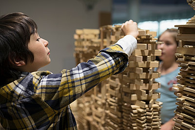 Boy and girl stacking wood pieces in science center - p1192m1194235 by Hero Images