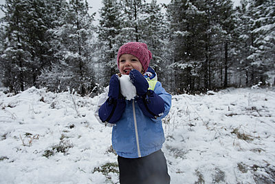 Girl holding snowball on beautiful snowy day - p1315m1421990 by Wavebreak