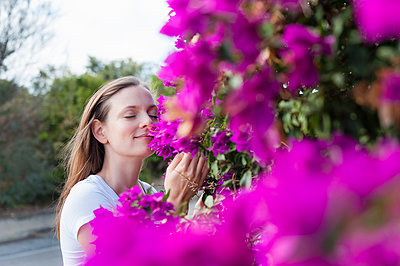 Portrait of woman with eyes closed smelling purple blossoms, Sardinia, Italy - p300m2198843 by Daniel Ingold