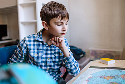 Boy with hand on chin studying map at table - p300m2267836 by Oxana Guryanova
