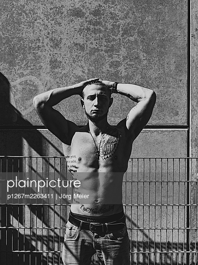 Man with tattoos on bare chest in the sunlight - p1267m2263411 by Jörg Meier