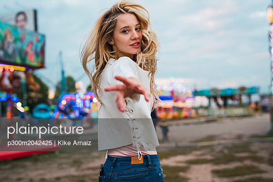 Young woman on a funfair reaching out her hand - p300m2042425 von Kike Arnaiz