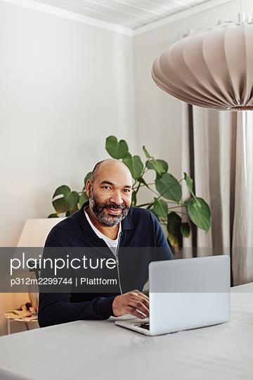 Smiling man using laptop at home - p312m2299744 by Plattform