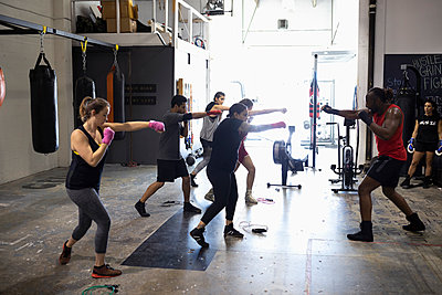 Instructor leading boxing class in gym - p1192m2033759 by Hero Images