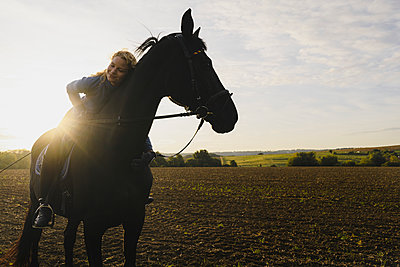 Affectionate woman on horse on a field in the countryside - p300m2155401 by Joseffson