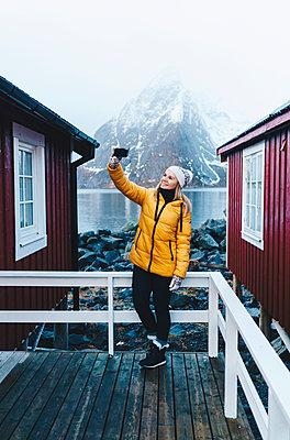 Tourist taking a selfie on a porch at Hamnoy, Lofoten, Norway - p300m2166327 by Daniel González