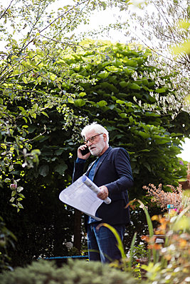 Senior man on the phone standing in garden with construction plan - p300m2188752 by Joseffson