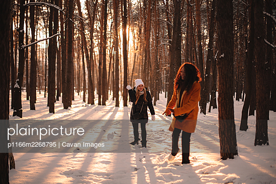 Happy female friends playing with snow in park during winter - p1166m2268795 by Cavan Images