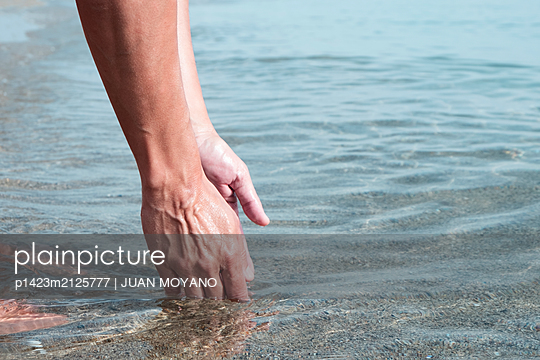 Man trying to catch some sea water in his hand - p1423m2125777 by JUAN MOYANO