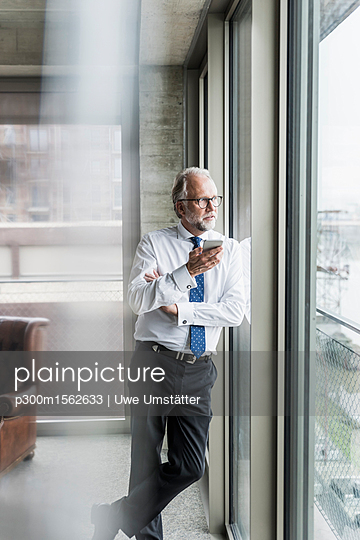 Mature businessman standing at the window holding cell phone - p300m1562633 by Uwe Umstätter