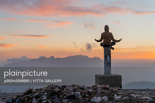Spain, Barcelona, Natural Park of Sant Llorenc, man sitting in yoga pose on pole at sunset - p300m2058583 by VITTA GALLERY