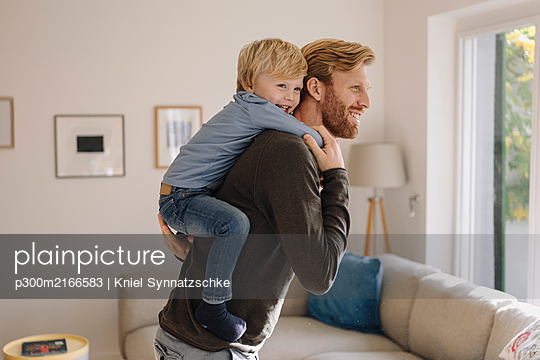Happy father carrying son piggyback at home - p300m2166583 von Kniel Synnatzschke