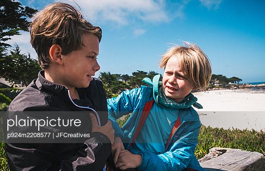 Two boys sitting by sandy beach near Carmel, California, USA, teasing each other. - p924m2208577 by JFCreatives
