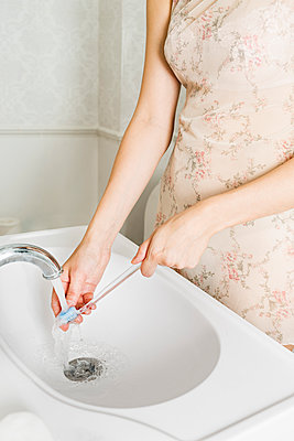 Midsection of woman washing toothbrush at bathroom sink - p301m1070101f by Vladimir Godnik