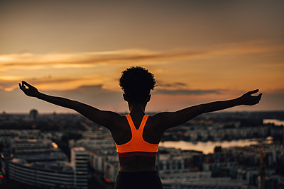 Female athlete with arms outstretched exercising during sunset - p426m2270856 by Maskot