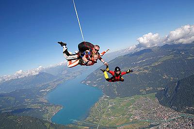 Smiling tandem sky divers holding hand with free faller, Interlaken, Berne, Switzerland - p429m1175408 by Oliver Furrer