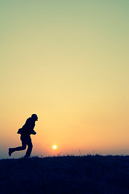 Side view silhouette of man running on field at sunset  - p794m2073036 by Mohamad Itani