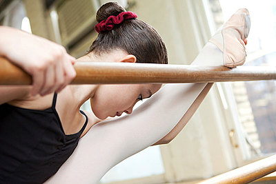 Ballerina stretching at barre - p9245498f by Image Source