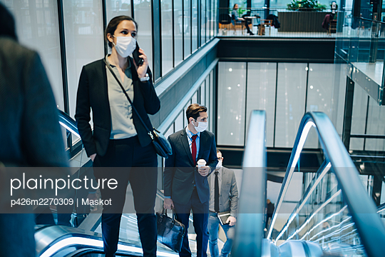 Businesswoman talking through smart phone while moving upwards on escalator during pandemic - p426m2270309 by Maskot
