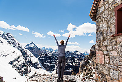 Exuberant female hiker on sunny, snowy mountaintop, Yoho Park, British Columbia, Canada - p1023m2066368 by Jarusha Brown