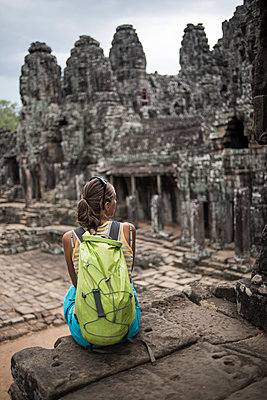 A female tourist at the Bayon, Ankor Thom temple, Angkor Wat, Siem Reap, Cambodia. - p1166m2107660 by Cavan Images
