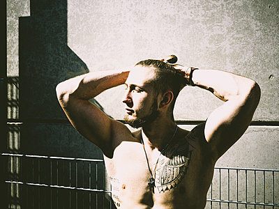 Man with tattoos on bare chest in the sunlight - p1267m2263398 by Jörg Meier