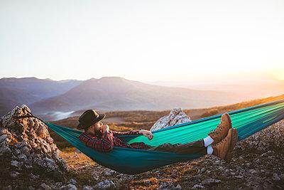 Man lying on hammock in mountain range - p1427m2163667 by Oleksii Karamanov