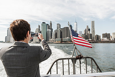 USA, Brooklyn, back view of businesswoman on a boat taking picture of Manhattan skyline - p300m1205081 by Uwe Umstätter