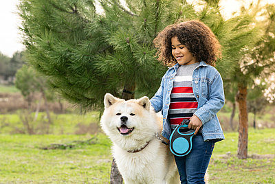 Smiling curly haired boy enjoying with dog in nature - p300m2265852 by Jose Carlos Ichiro