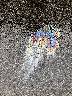 Colorful oil spill on wet pavement - p301m2202385 by Norman Posselt