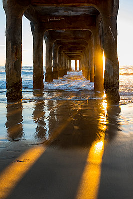 View underneath Manhattan Beach pier at sunset, Los Angeles, California, USA - p343m1569085 by Sean Davey