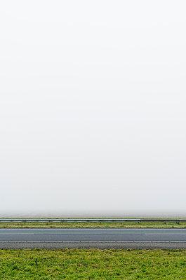 Motorway in heavy fog, Arnemuiden, Zeeland, Netherlands - p429m1227030 by Mischa Keijser