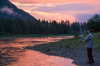 Teenage boy fishing in river at sunset, Washington, USA - p924m1422711 by Raphye Alexius