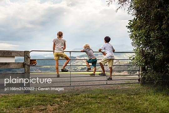 Three kids climbing on a gate with mountains in the distance - p1166m2130922 by Cavan Images
