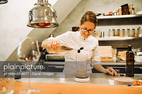 Female chef in uniform working at kitchen counter in a restaurant - p1166m2208077 by Cavan Images