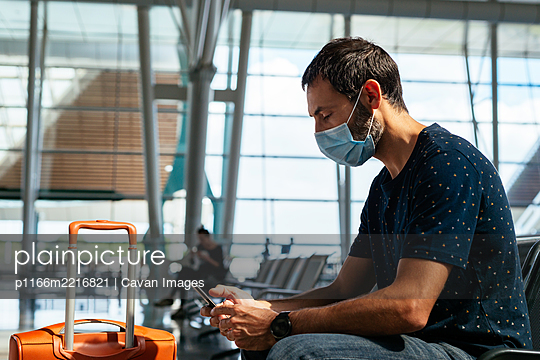 Young man wearing a face mask looking at his phone at the airport - p1166m2216821 by Cavan Images