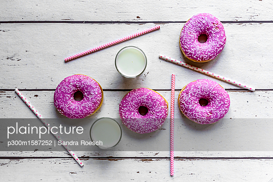 Four pink doughnuts, two glasses of milk and straws on white wood - p300m1587252 von Sandra Roesch