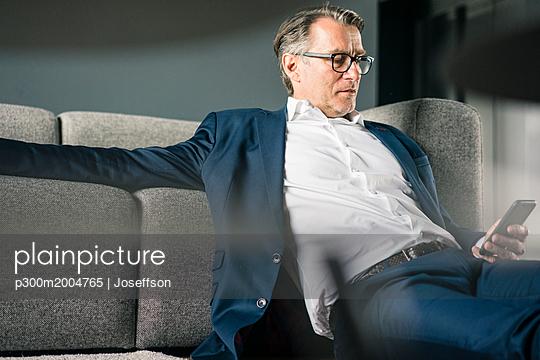 Mature businessman sitting on couch using cell phone - p300m2004765 von Joseffson