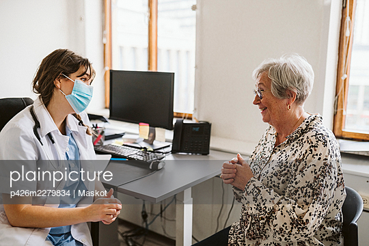 Smiling senior female patient talking with medical expert wearing face mask - p426m2279834 by Maskot