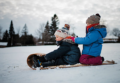 Side view of siblings on sled against cloudy sky - p1166m1534310 by Cavan Images