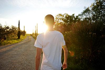 Jugendlicher mit Kurzhaarschnitt auf einem Feldweg - p1468m1585006 von Philippe Leroux